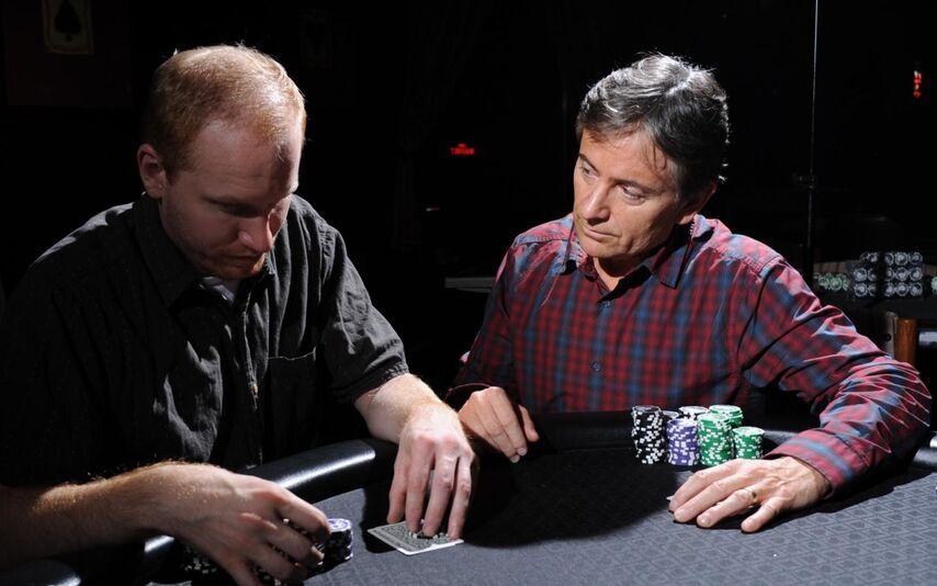 Игрок слева обдумывает ставку. Игрок справа сидит в защитной позе, словно пытается запугать противника и отговорить от ставки.