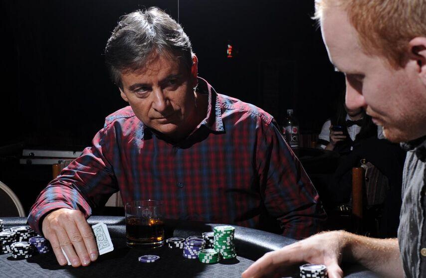 Игрок слева только что блефовал. Пытаясь отговорить противника от колла, он держит свои карты так, словно готов перевернуть их и сравнить с картами соперника.