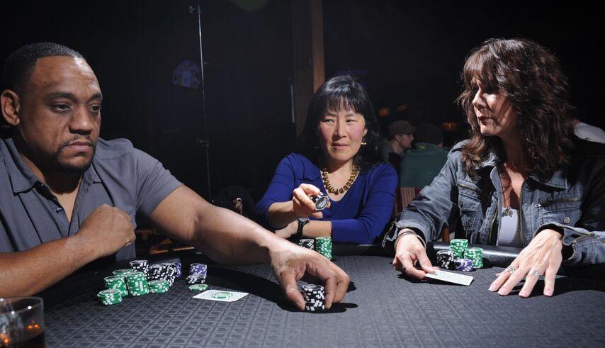 Мужчина делает ставку. Женщина справа сигнализирует о намерении сделать фолд, повышая вероятность того, что женщина посередине сделает колл.